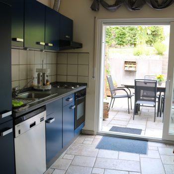 Voll eingerichtete Küche mit Blick auf die Terrasse